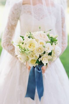 White wedding bouquet with roses, gardenias, and larkspur tied with blue ribbon | Abby Jiu | Brides.com