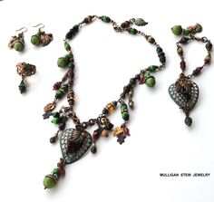 A Parure four piece set.  Crisp Fall colors that include leaves, charms, glass beads and more.  A Necklace, Bracelet, Earrings and Ring.  Kate from MulliganStewJewelry.com