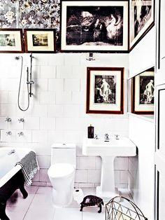 White tiled bathroom with framed prints.