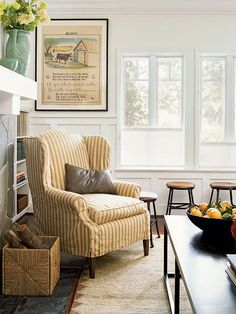 This casual living room invites guests to relax. Get the look with a simple, slipcovered chair and a playful, vintage poster. Short stools under the window sill provide extra seating for adults or little ones. (Photo: Dominique Vorillon)