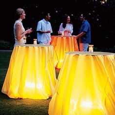 Battery powered camping lanterns under tables with plastic party tablecloths. Affordable outdoor ambiance