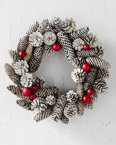 Two words: winter wonderland. Create your own with this stunning wreath handcrafted using frosted glass ornaments and lightly spray-painted pinecones.