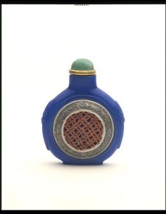 [Snuff bottle] Moulded and carved blue glass, with two porcelain medallions painted with enamel colours  [Stopper] Porcelain, coloured white and green