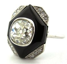 Art Deco era platinum and Old Cut diamond engagement ring in geometric form featuring a 1.75 Carat Old Mine Cut diamond with black onyx and round cut diamond accents