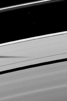 The shadow of the moon Mimas is cast on Saturn's outer A ring in this image which also shows a couple of moons and a collection of stars.    Atlas (30 kilometers, or 19 miles across) can be seen in the top right of the image, between the A ring and thin F ring. Pan (28 kilometers, or 17 miles across) can be seen orbiting in the Encke Gap in the lower left of the image. Mimas is not shown.