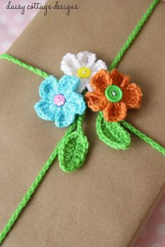 This FREE! crochet pattern for this adorable gift wrapping idea is perfect for spring and summer. Made from crocheted daisies and a leaf chain, it's sure to get attention at your next party! #giftwrap #crochetidea @Lauren @ Daisy Cottage Designs