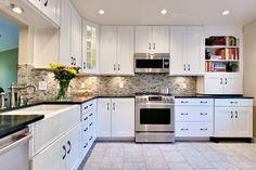 Black granite, white cabinets, black knobs, light backsplash