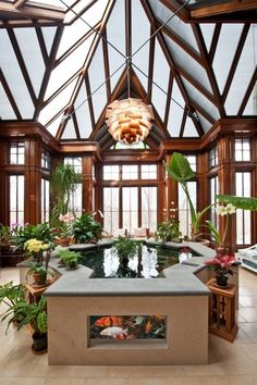 Amazing conservatory with a unique multi-vaulted ceiling, tall windows, and a koi pond