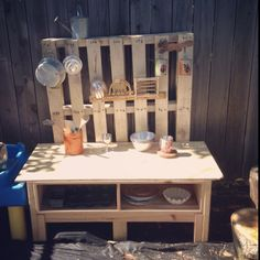 Outdoor pallet play kitchen... Used an old tv stand and placed a pallet behind it, added some hooks and viola!