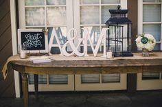 We love the rustic simplicity of this guest book table {Leif Brandt Photography } rustic guest book table, guestbook table lantern, welcome table, guest books, wood letters, wedding rustic, rustic simplic, guest table, memory table
