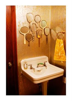 Cute idea for wall decor in Lucille's water closet - vintage hand mirrors