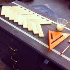Create a herringbone pattern on top of a ugly dresser with paint sticks.