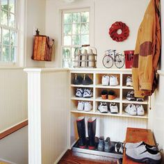 On a formerly empty stair landing, a compact mudroom was made possible by replacing open railings with half walls and creating a recess for a boot bench. | Photo: Tria Giovan | thisoldhouse.com