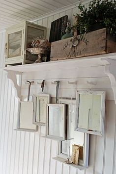 Collection of square mirrors hanging from a hook shelf