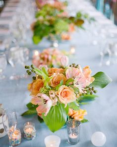 Warm fruit and floral arrangements add a pop of color on top of pale blue linens