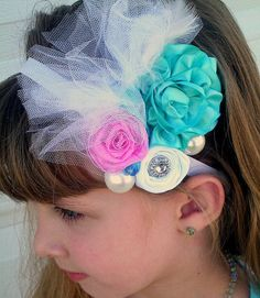 hair clip. Can be clipped in the hair. or to the headband. Or even to a cardi, or shrug.