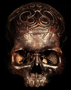 DAYAK TRIBE: HEAD HUNTING HUMAN TROPHY SKULL #4  HAND CARVED HUMAN SKULL.  THE DAYAK TRIBE, FROM BORNEO ISLAND  INDONESIA, CARVE DESIGNS INTO THE SKULLS  OF THEIR HEADHUNTED VICTIMS AND INSERT WOODEN FIGURES.