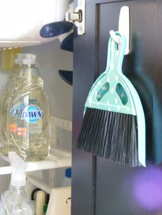 Dollar Store dust pan and brush hanging on a command hook in cabinet. Love.