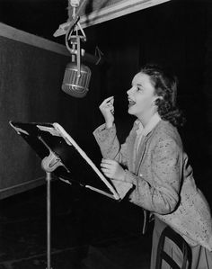 """Judy Garland sings in a recording session for THE WIZARD OF OZ, which features what became her signature song, """"Over the Rainbow."""" The song earned an Oscar for the famous musical pairing of composer Harold Arlen and lyricist E. Y. Harburg."""