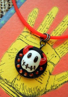Fun, easy DIY Stitched Devil Mosaic Necklace.  Small red orange cubic zirconia beads, and a lampwork bead of a little devil head with a stitched mouth are set inside a black gunmetal bezel using EnCapture Artisan Concrete.  The pendant is hung on a Silkie cord.  All parts available at www.rings-things.com