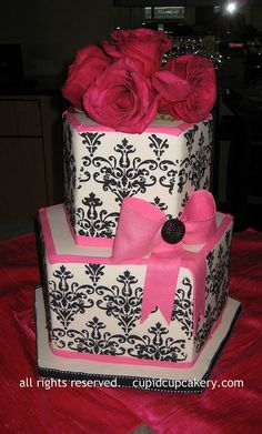 Damask Cake. Pentagon shaped cakes, white fondant stencilled with black royal icing and trimmed in hot pink, with a hot pink bow. Fresh roses for the top.