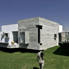 A glass bridge connects a concrete house with wonky windows to an artist's studio in Puebla, Mexico.