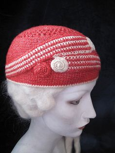 1920s coral red and white crocheted cloche with a graphic Art Deco design featuring 1 1/8-inch wide belts that overlap and end in spiral disks. There is a lacy ring of pointelle around the spiraled crown