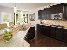 Dark kitchen cabinets; inspired by the light fixtures.