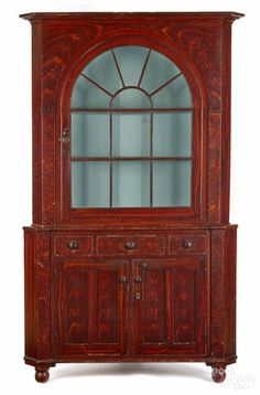 Winning bid:$2,600  Pennsylvania painted two-part corner cupboard, mid 19th c., probably York County, retaining its original flame grained surface, 92'' h., 55'' w. - Price Estimate: $1500 - $2500