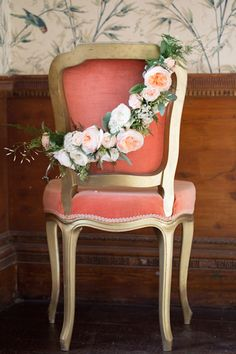 Coral chair with floral garland via Bridal Musings
