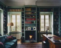 2021  desiretoinspire.com (Simon Watson)    This traditionally-furnished library appears to be completely enveloped in grayish-green-painted wood books shelves with handsome moldings and trim work. But the room leaves plenty of space for a cozy fireplace, a desk for studying and a comfortable couch for reading. A homey, pleasant room.