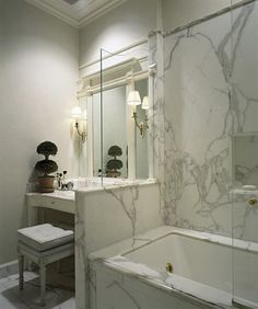 Elegant small space solution: glass partition and pony wall separating tub and vanity.