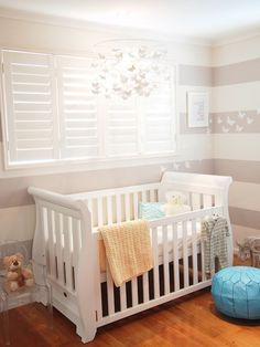 Adorable boy's nursery design with white and gray horizontal striped walls as well as Pottery barn Kids Butterfly Chandelier over white sleigh crib placed under window accented with Ghost Chair and Turquoise Moroccan leather pouf.