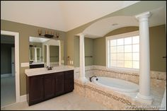 His and hers style master bath with barrel vault tub design - best ideas for how to design with white columns inside your home.