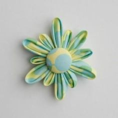 DIY brooch flowers. I like these…I've never seen a fabric flower quite like this!