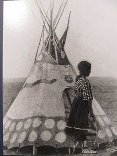White Calf from the All Tall People Blackfoot clan stands in front of  a child's tipi wearing a fabric dress decorated with shells and trade  beads.
