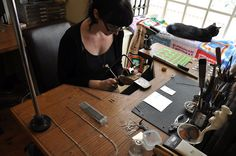 Sim Luttin at her workbench with her cat Kinski