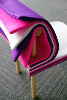"""Inspired by books, the Pages chair allows the user to adjust the seat height and backrest cushioning simply by turning its colorful padded """"pages."""""""