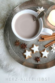 Christmas stars on a hot-drink tray (cinnamon stars, star anise, paper moravian stars)