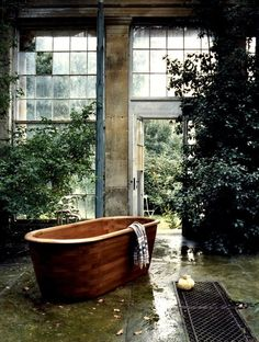 Warm wooden tub in a rustic room.