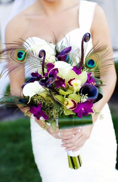 peacock feathers and purple lilies n orchids  I absolutely love this bouquet!! (minus that random green roll in the front center).