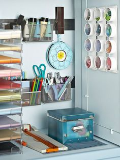 """Easy Cabinet Organizers  Use coordinated baskets & tins to hold essential items in a decorative way. Small round containers are perfect for organizing & color-coding. Editor's tip: Hang metal strips on the wall and attach magnets to metal mesh containers to store paintbrushes, markers, scissors, & paint. This uses wall space efficiently & keeps little things organized & visible."""