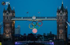 The full moon rises through the Olympic Rings hanging beneath Tower Bridge