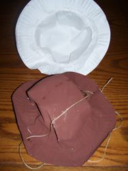 Cowboy Hat from Paper Plates        Take two paper plates.  Cut the center out of one plate.  Take the   edges of the intact paper plate and staple it around the cut edge of the   paper plate.  You will need to make a couple folds in the paper plate that   creates the crown as you continue to staple it in place.  Hole punch two   holes in the brim as shown.  Paint the hats.  Let them dry then string a   piece of string through the holes.  Be aware that the string may be   considered a strangulat