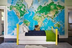 boy's rooms - Toys R Us World Map Mural bright yellow twin bed navy blue blanket green fringe throw gray rug Fun boy's bedroom with Toys R Us