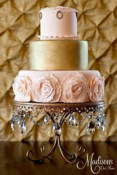 Elegant rose and gold cake with rosettes on the bottom tier. Lovely gold cake stand with crystal detail.