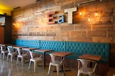 Restaurant interior. Reclaimed channel letters Eat sign, tufted benches, exposed filament bulbs, walnut butcher block tables, Tabouret metal chairs, concrete floors.