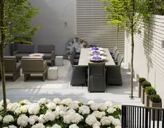 Kelly Hoppen garden with horizontal slatted fencing, trees growing through deck, and white hydrangeas