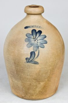 """Price Realized: $ 632.50 One-Gallon Cobalt-Decorated Stoneware Jug, Stamped """"WM. MOYER,"""" Harrisburg, PA origin, circa 1855, ovoid jug with squared spout and applied strap handle, decorated with a brushed cobalt daisy. Flake to underside. Some crazing to surface. H 11""""."""