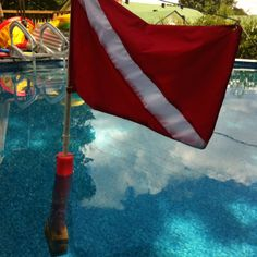 "My homemade dive flag.    Thanks Cori for sewing the flag!!  I used 3/4 PVC pipe, half a swimming noodle, three bricks, 1 PVC T joint, 1 PVC pipe joint, 1 - 4"" 1/4 bolt with locking nut and a quick release pin.   I was able to use my pool to balance the weight & foam ratio.   Fun project!!!"
